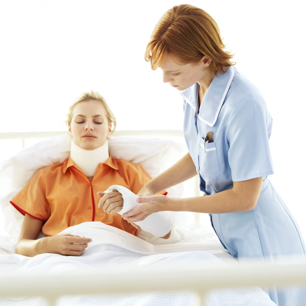 Young Nurse Tending to Young Woman with Neck Brace and Arm Cast --- Image by © Royalty-Free/Corbis